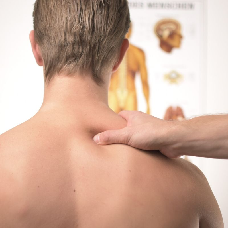 back of man with chiropractor's hand on neck