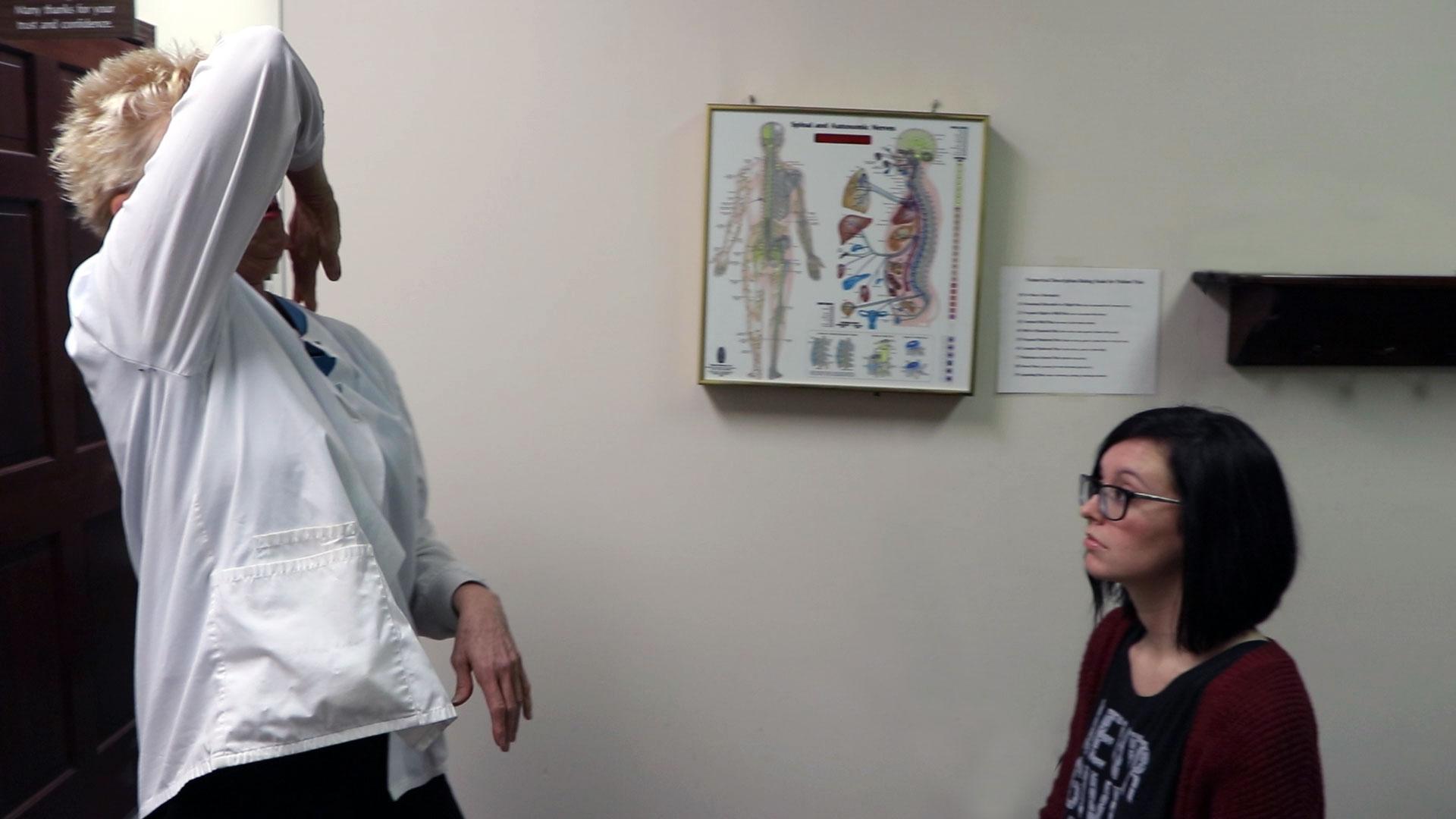 chiropractor demonstrating shoulder movement to patient